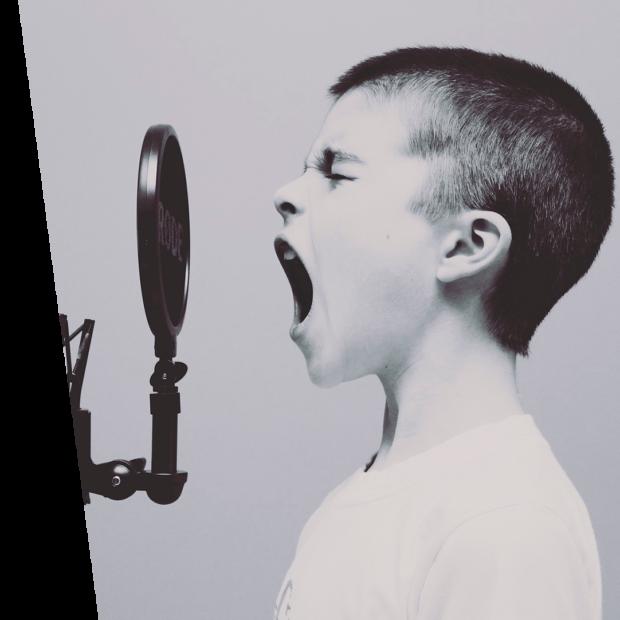 Un niño gritando en un micrófono que representa el servicio de marketing digital de una empresa SEO en Madrid